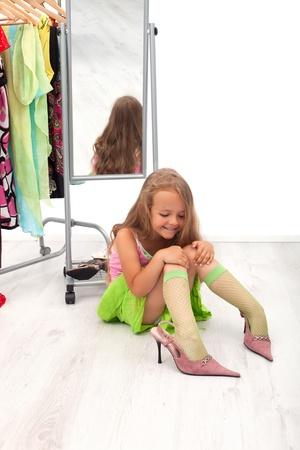 przewymiarowany: MaÅ'a dziewczynka siedzi na podÅ'odze próbuje na wysokim obcasie Zdjęcie Seryjne
