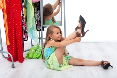 innocence: Little girl having fun trying her mothers shoes and clothes Stock Photo