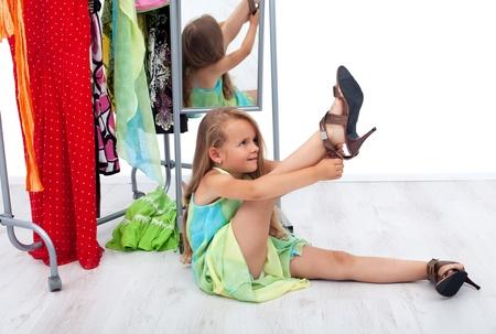 przewymiarowany: Mała dziewczynka po próbuje zabawa matki buty i ubrania