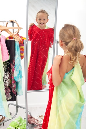Trying on dresses is fun - little girl in front of the mirror photo