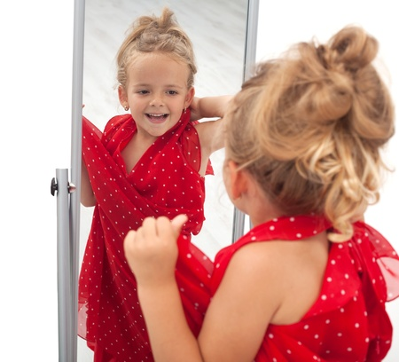 imitations: Little girl trying large dress in front of mirror - isolated
