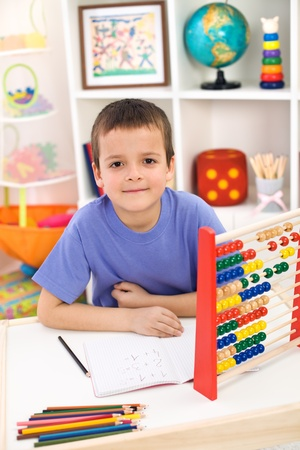 Boy preparing for elementary school doing exercises at home photo