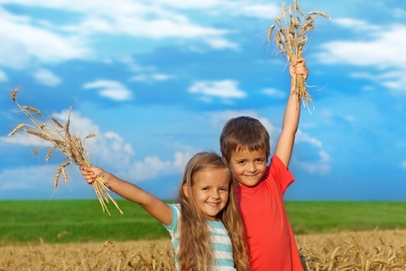 blue sky and fields: Kids outdoors in wheat field against blue sky waving happily