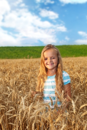 blue sky and fields: Little golden hair girl on wheat field in late afternoon lights smiling