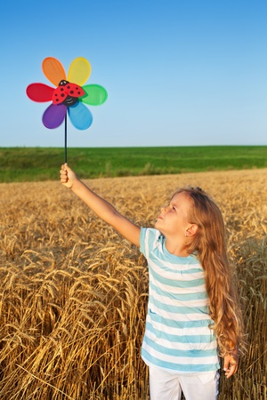 Little girl playing outdoors in summer time with a windmill toy photo