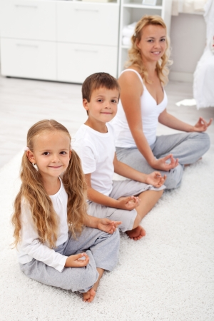 Happy smiling kids doing yoga relaxation at home with their mother - focus on the little girl photo