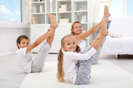 Healthy morning stretching - woman with kids doing gymnastic exercise at home photo