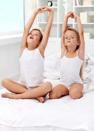 pijama: Niños despertarse y estirar los brazos en la cama Foto de archivo