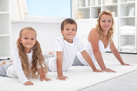 Woman and kids stretching their backs doing gymnastic exercises at home - focus on the boy photo