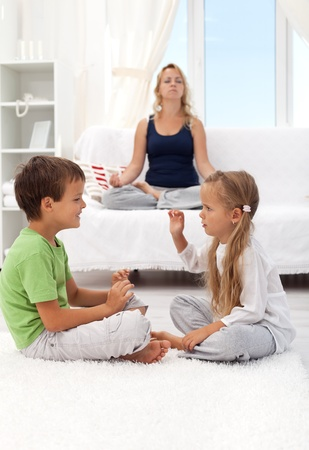 sibling rivalry: Woman trying to relax with two quarreling child - focus on the boy, motion blur on the girl