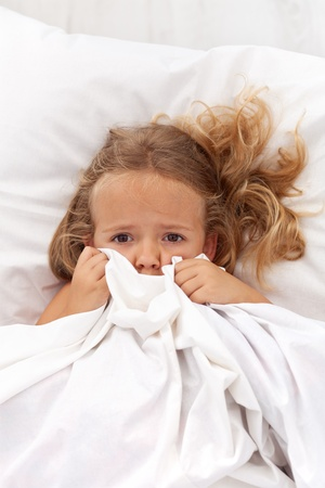 frighten: Little girl having childhood nightmares and fears hiding under the quilt
