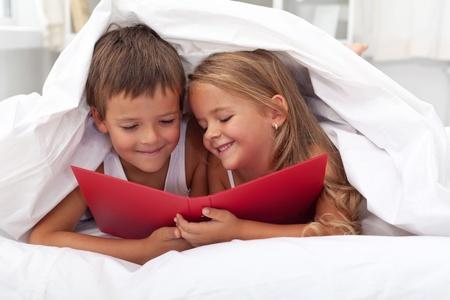 pajamas: Disfrutando el conocimiento prohibido - ni�os leyendo en la cama bajo el tejido