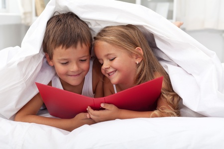 child in bed: Enjoying the forbidden knowledge - kids reading in bed under the quilt