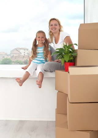 conceptual cute: Happy woman and little girl in a new home sitting on windowsill with boxes and plant - moving theme Stock Photo