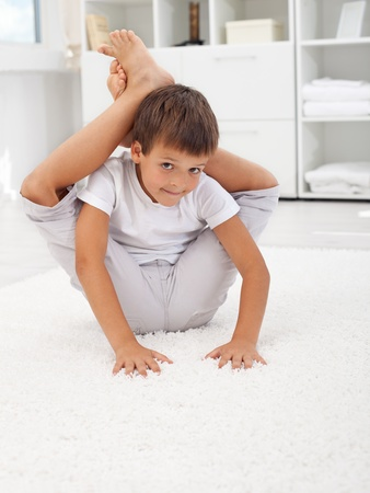 contortionist: Little contortionist boy bending himself in his room Stock Photo
