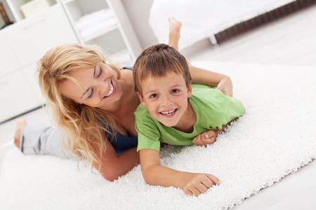 깔개: 행복 한 엄마와 바닥에 거실 레슬링에서 재생 아들 스톡 사진