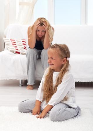 petite fille triste: Petite fille ayant un acc�s de col�re avec sa m�re d�sesp�r�e en arri�re-plan Banque d'images