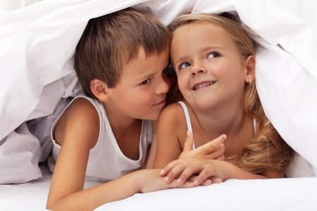 Kids planning the next prank hidden under the quilt photo