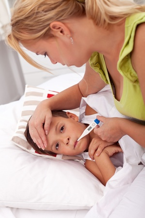 Woman checking little laying boy's temperature Stock Photo - 10409225