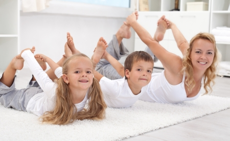 family line: Family doing stretching exercises laying on the floor - healthy lifestyle