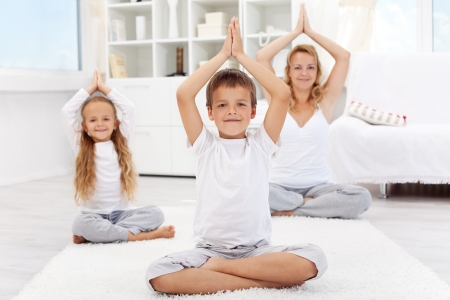 Happy balanced life - woman and kids doing yoga exercise at home - focus on boy photo