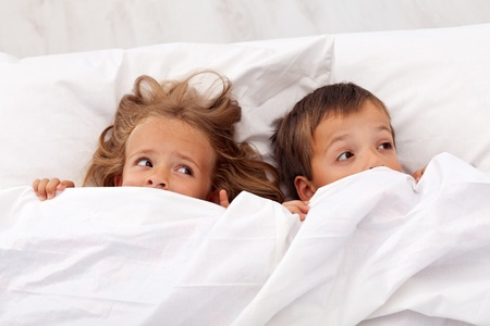 frighten: Kids afraid laying in bed and pulling the quilt on their heads Stock Photo