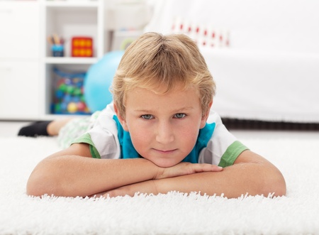 Beautiful kid resting on the floor propping his head Stock Photo - 10480645