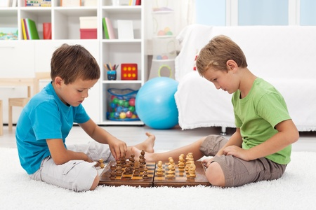 jugando ajedrez: Niños jugando al ajedrez sentados en el piso de su habitación