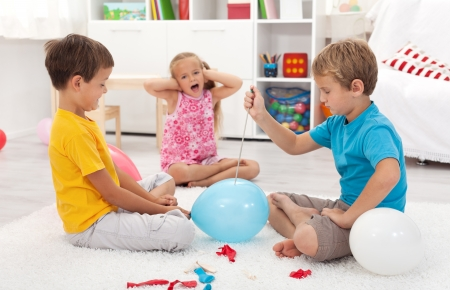 Kids popping balloons in their room fearing the blast - focus on the right side boy Stock Photo - 10480650