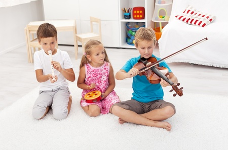 playing music: Kids trying to play on different musical instruments sitting on the floor