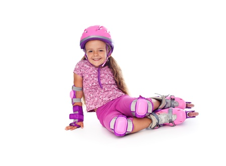 rollerskating: Happy little girl with roller skates and protective gear resting - isolated Stock Photo