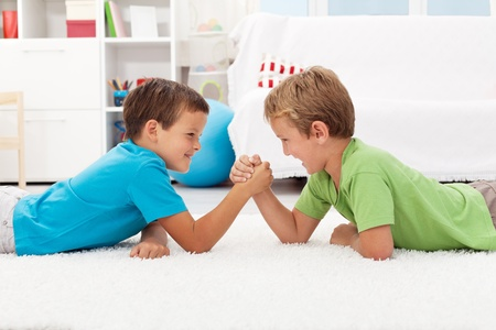 Boys arm wrestling in the kids room - childhood rivalry photo