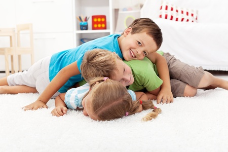 piled: Happy wrestling kids laying in a pile indoors - focus on the middle child