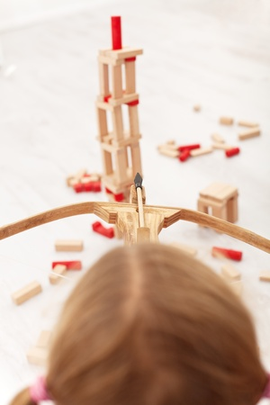 Kid shooting down a wooden blocks building with bow and arrow toy - top view