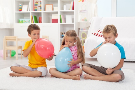 Three kids blowing large balloons sitting on the floor photo