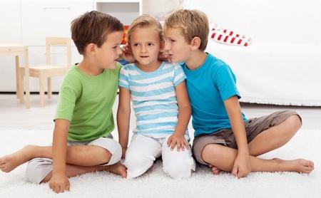 Boys whispering to a girl childish secrets - indoors scene photo