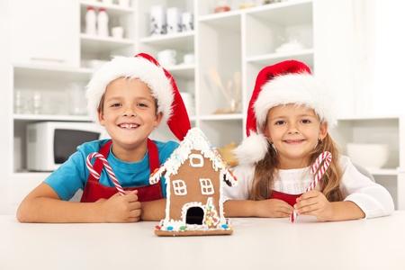 casita de dulces: Ni�os felices en la �poca de Navidad en la cocina con su casa de pan de jengibre