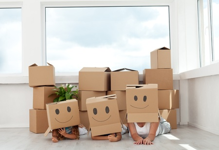 Family having fun with cardboard boxes moving into their new home photo