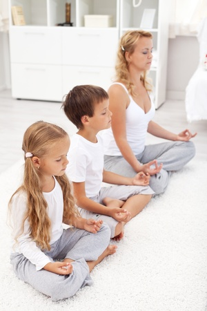 Happy healthy life concept with family doing relaxation exercise at home photo