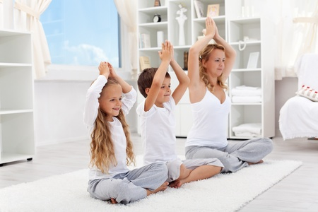 Balanced life - woman with kids doing yoga relaxation exercise at home