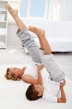 Healthy life education by example - little boy and his mother exercising at home photo