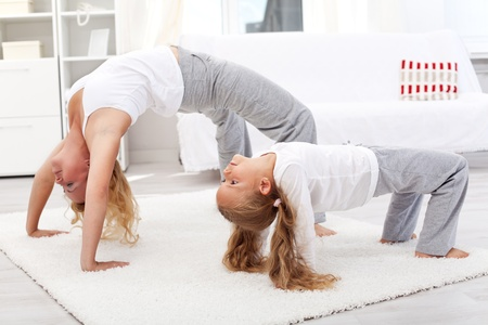 Healthy life education by example - woman and little girl exercising together photo