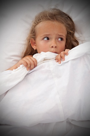 agonizing: Little girl in bed awaken by nightmares laying scared Stock Photo