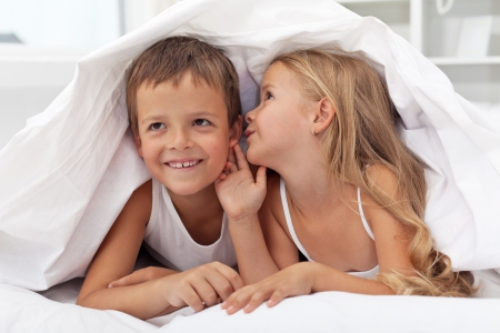 Happy smiling kids sharing their secrets under the quilt photo