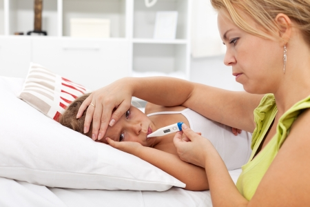 Sick kid with high fever laying in bed and mother taking temperature photo