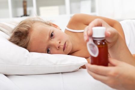 ragazza malata: Malata in attesa del suo farmaco posa a letto Archivio Fotografico