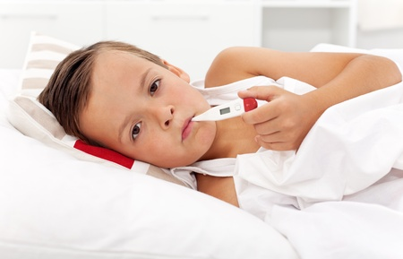 caucasian fever: Sick boy with thermometer laying in bed and taking temperature Stock Photo