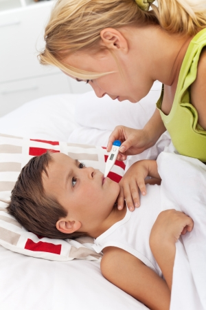 Sick boy laying in bed and his mother taking temperature Stock Photo - 10744865