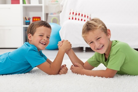 Happy kids laughing and arm wrestling - focus on the left boy Stock Photo - 10744867