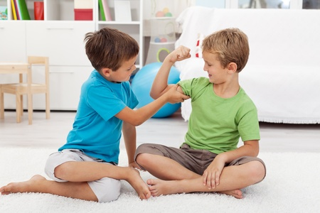 buddies: Boys showing off with the size of their biceps sitting on the floor at home